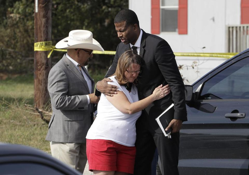 Pastor Dimas Salaberrios, right, prays with Sherri Pomeroy near the First Baptist Church of Sutherland Springs, Monday, Nov. 6, 2017, in Sutherland Springs, Texas. A man opened fire inside the church in the small South Texas community on Sunday, killing and wounding many. The Pomeroy's daugher, Annabelle, 14, was killed in the shooting. (AP Photo/Eric Gay)