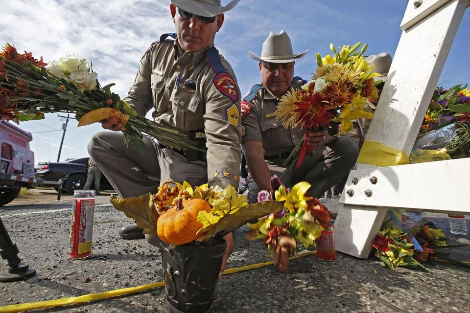 Mandatory Credit: Photo by LARRY W. SMITH/EPA-EFE/REX/Shutterstock (9195275z) Texas State Troopers pick up flowers left for a memorial to move them out of the street near the church while investigators work at the scene of a mass shooting at the First Baptist Church in Sutherland Springs, Texas, USA, 06 November 2017. A single gunman identified as Devin Patrick Kelley, 26, is suspected of killing 26 people including several children as they attended church 05 November 2017. Kelley was found dead in his vehicle after a brief chase, however the cause of his death is unclear. Mass shooting in Texas, Sutherland Springs, USA - 06 Nov 2017