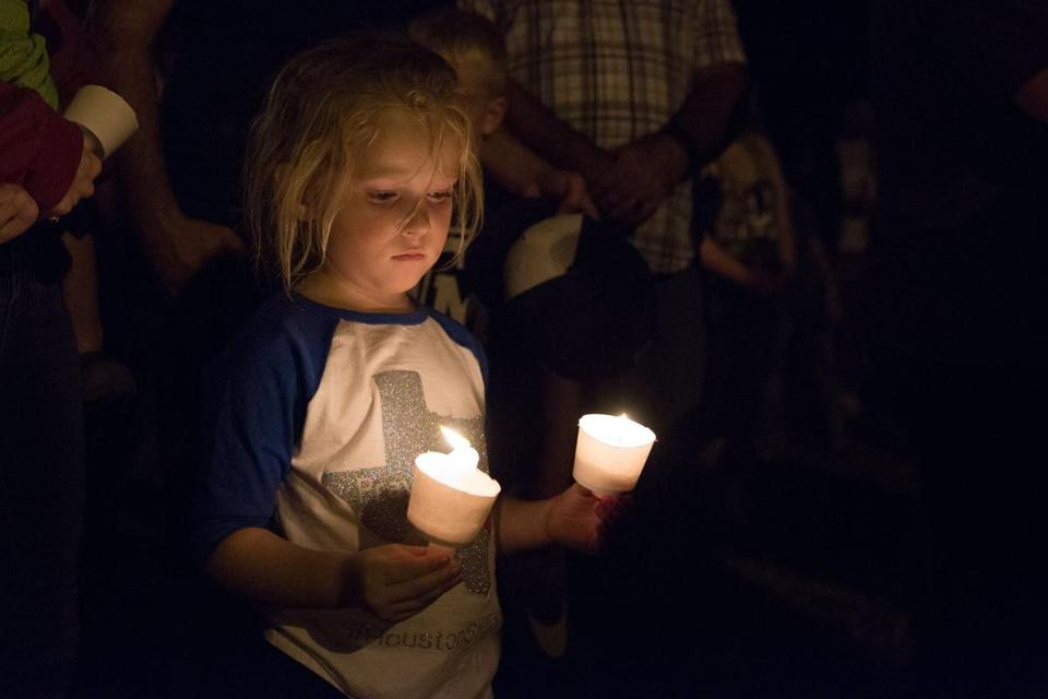 A child held candles Sunday during a vigil in Sutherland Springs, Texas, site of a mass shooting.