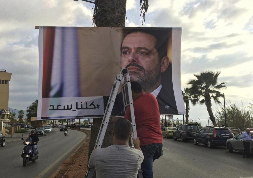 "Workers hang a poster of outgoing Prime Minister Saad Hariri with Arabic words that read, ""We are all Saad,"" at a seaside street in Beirut, Lebanon, Thursday, Nov. 9, 2017. Hezbollah has called on Saudi Arabia to stay out of Lebanese affairs, saying the resignation of Prime Minister Saad Hariri, announced from Riyadh over the weekend, ""has raised many questions."" (AP Photo/Hussein Malla)"