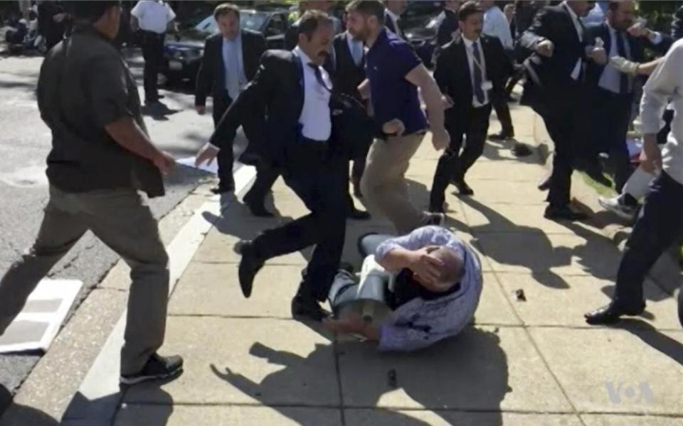 In this frame grab from video provided by Voice of America, members of Turkish President Recep Tayyip Erdogan's security detail are shown violently reacting to peaceful protesters during Erdogan's trip last month to Washington. House Republican and Democratic lawmakers are expected to approve overwhelmingly a resolution that calls for members of Erdogan's security detail who were involved in the incident to be brought to justice. The vote is slated for Tuesday evening. (Voice of America via AP)