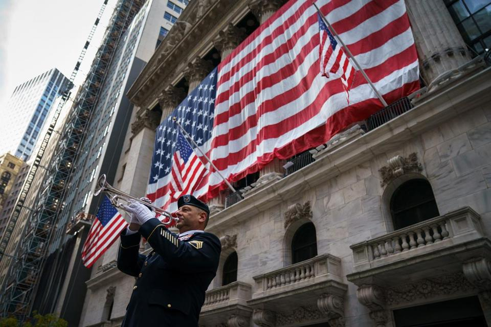 NEW YORK, NY - NOVEMBER 10: Mario Tronti, a member of the 42nd Infantry Division of the U.S. National Guard, performs 'Taps' as an American flag is raised on the facade of the New York Stock Exchange (NYSE), November 10, 2017 in New York City. The United States will mark Veterans Day this Saturday, November 11. (Photo by Drew Angerer/Getty Images)