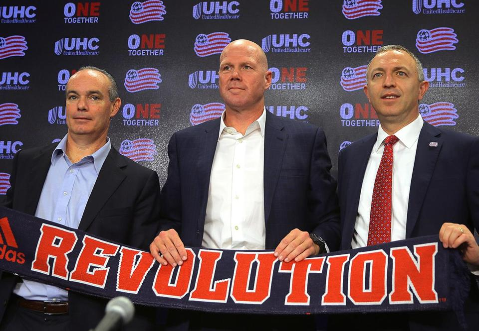 Foxborough, MA - 11/13/2017 - At the close of the press conference, a banner is held. Flanked by the Revolution general manager Michael Burns (cq), left, and president Brian Bilello (cq), right, Brad Friedel (cq) is introduced as the new head coach, at Gillette Stadium. Photo by Pat Greenhouse/Globe Staff Topic: 14Revolution Reporter: Frank Dell'Apa