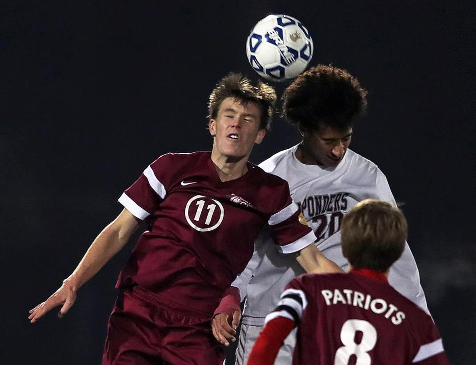 Lynn, MA: 11-13-17: Concord-Carlilse's Cameron Emde-Gerdine (11,left) and Arlington's Dominic Black (20,right) go for a first half header. Arlington took on Concord-Carlisle in the Division Two North sectional high school soccer finals held at Manning Field. (Jim Davis/Globe Staff)