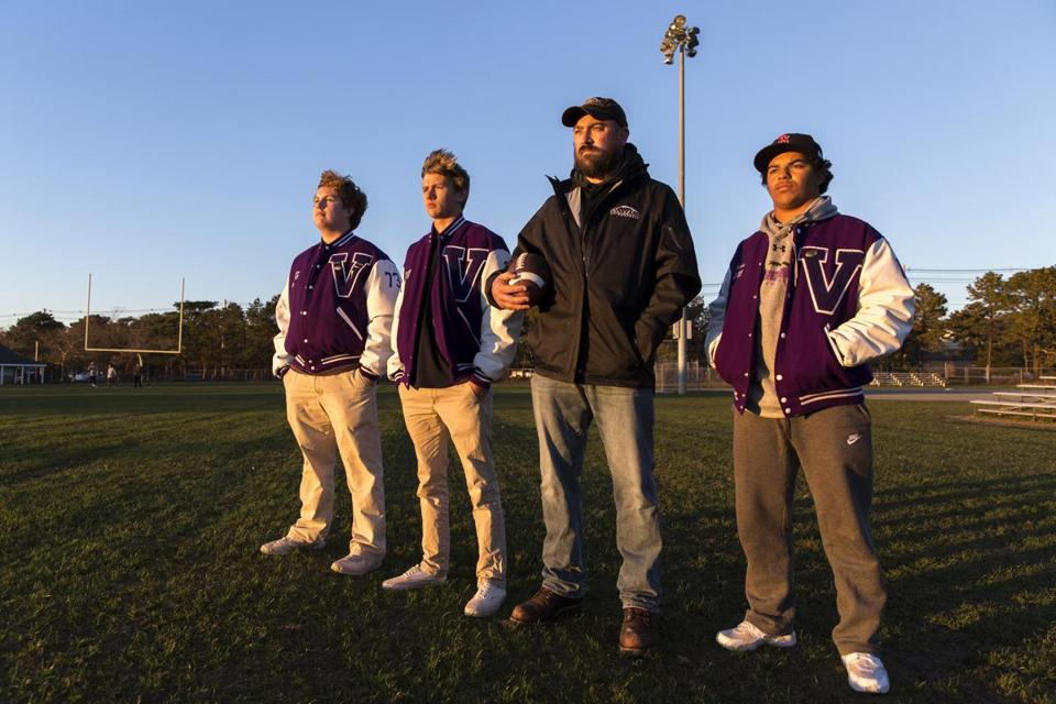"Martha's Vinyeard Regional High School football coach, Ryan Kent (3rd from left) is photographed with players, Sam Rollins, 18, Cooper Bennett, 17, and Zachary Moreis, 17, all of Edgartown, MA, on the football field after their season was cancelled prematurely due to not having enough uninjured players. ""We're all mourning the loss of a season that ended too soon,"" says coach Kent. ( Julia Cumes for The Boston Globe )"
