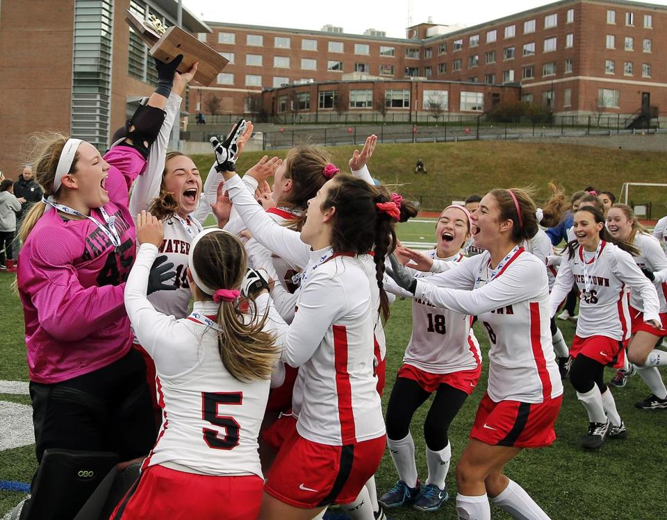 Watertown's Sydney Poulin and Jonna Kennedy (45) hold up the trophy as they celebrate after defeating Oakmont 5-1 during their D2 state final in Worcester, Mass., Saturday, Nov. 18, 2017. (Winslow Townson for The Boston Globe)