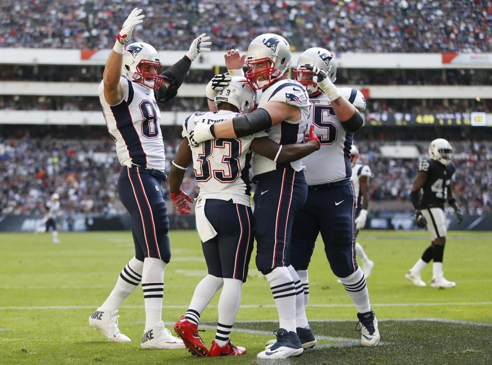 Mexico City, Mexico -- 11/19/2017 - (L-R) New England Patriots Rob Gronkowski comes in to celebrate teammate Dion Lewis' touchdown with Joe Thuney and Ted Karras during the first half of their 2017 NFL Mexico Game against the Oakland Raiders at the Estadio Azteca. (Jessica Rinaldi/Globe Staff) Topic: Patriots Reporter: