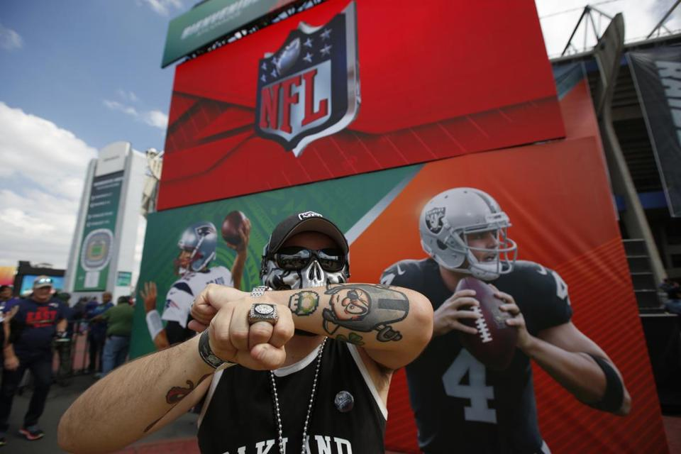 A Raiders fan shows off his rings and tattoos before the game.
