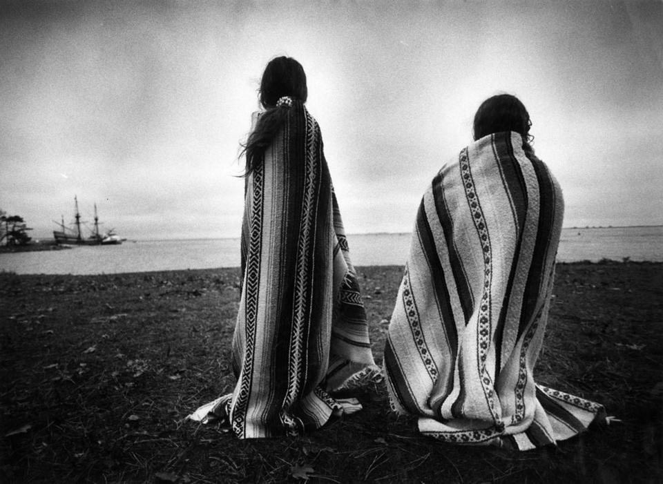 Plymouth, MA - 11/26/1992: Weetoomoo Carey, 8, left, and her sister Jackolynn Carey, 5, Wampanoag Nipmucs from Mashpee, look across to the Mayflower replica anchored near Plymouth Rock in Plymouth, Mass. on Nov. 26, 1991. They were with a group of Native Americans gathered for a day of mourning in counterpoint to the Pilgrims' Thanksgiving. (Suzanne Kreiter/Globe Staff) --- BGPA Reference: 141128_MJ_003