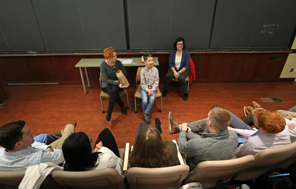 Braeden Yee, 11, talks with a group of students at BU's School of Medicine.