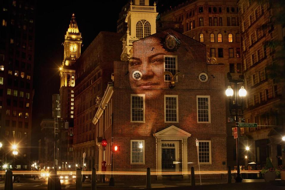"A image from the ""Boston #StandsWithImmigrants"" art project, which features portraits that have been projected around the city."
