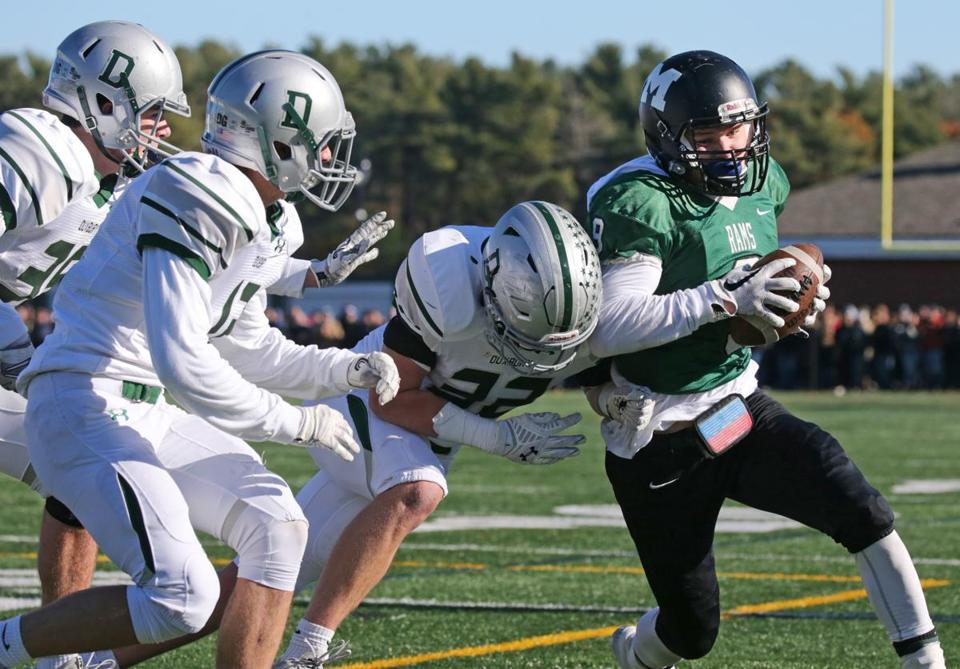 Marshfield's Jack McNeil tries to get around the corner against Duxbury's defense.