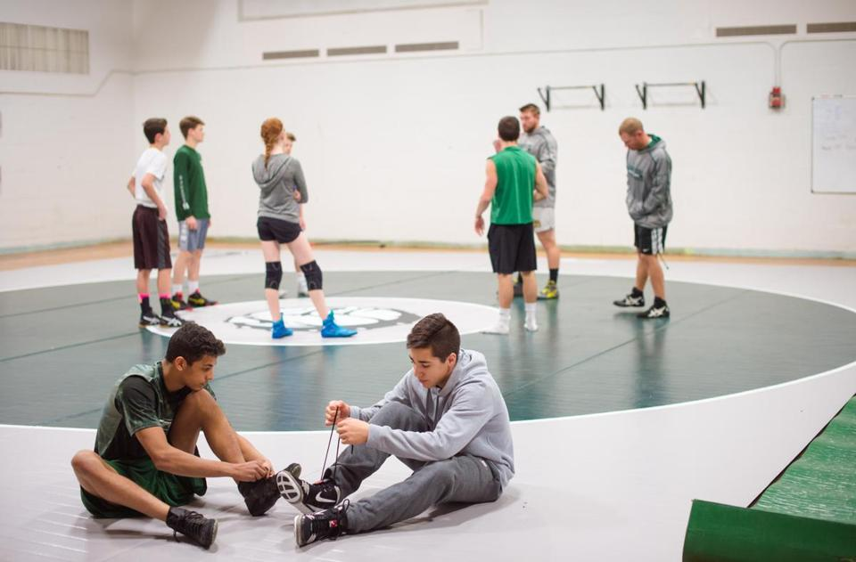 Canton High School wrestler Eddie Marinilli, right, laces up for practice in Canton, Mass., Monday, Nov. 26, 2017. At left is wrestling teammate Anis Chakir. Gretchen Ertl for The Boston Globe.