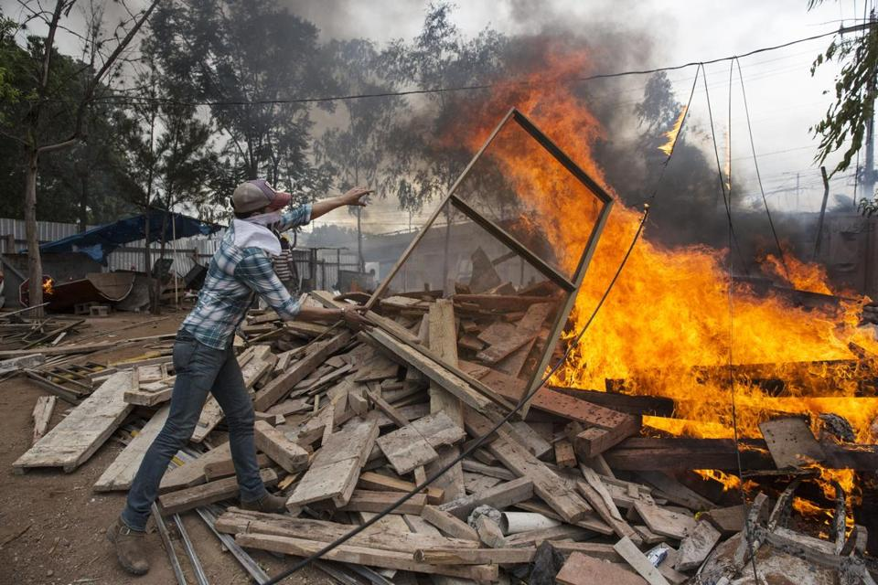 A supporter of opposition presidential candidate Salvador Nasralla throws wood on a fire using materials stolen from a warehouse, near the institute where election ballots are stored in Tegucigalpa, Honduras, Thursday, Nov. 30, 2017. Protests are growing as incumbent President Juan Orlando Hernandez emerged with a growing lead for re-election following a reported computer glitch that shut down vote counting for several hours. (AP Photo/Fernando Antonio)