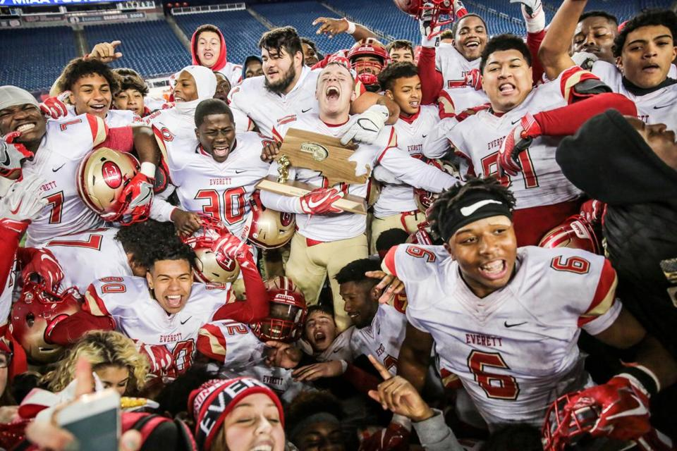 Everett celebrates with the MIAA trophy after completing its perfect season with a 35-10 win over Xaverian in the Division 1 Super Bowl.
