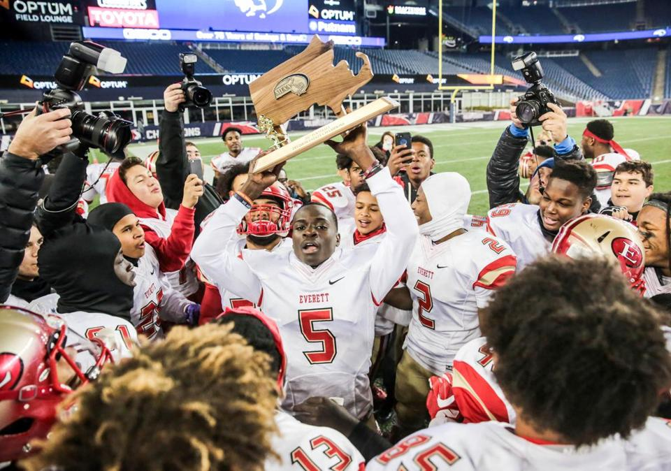 12/02/2017 FOXBOROUGH, MA Mike Sainristil (cq) 5, holds the trophy as Everett celebrates their victory after a game between Everett and Xaverian at the MIAA State Football Championships held at Gillette Stadium in Foxborough. (Aram Boghosian for The Boston Globe)
