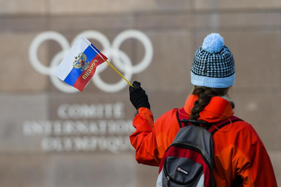 A woman holds a Russian flag in front of the Olympic Rings logo during the Executive Board meeting, at the International Olympic Committee (IOC) headquarters, in Pully near Lausanne, Switzerland, Tuesday, December 5, 2017. (Christophe Bott/Keystone via AP)