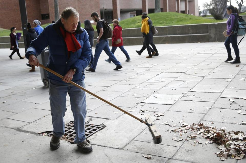 Boston, MA -- 11/30/2017 - Bob Carroll, a longtime janitor at UMASS Boston, sweeps leaves on campus. Carroll is among the 40 people getting laid off. (Jessica Rinaldi/Globe Staff) Topic: 01janitor Reporter: