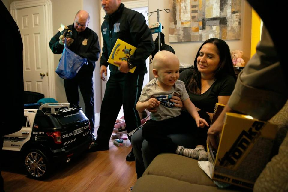 Sandra Cordero (right) held her son, Edison, as he admired gifts from members of the Chelsea Police Department that were brought to his home. Edison and his toddler-size cruiser are now honorary members of the force.