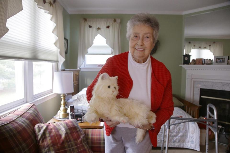 "Mary Derr, 93, held her robotic cat in her South Kingstown, R.I., home. Hasbro wants to enhance its ""Joy for All"" cat to assist seniors, and the toymaker and Brown University have received a three-year, $1 million grant."