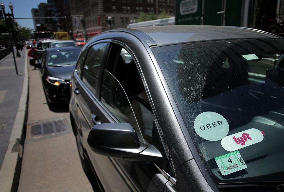 A driver with placards for both Lyft and Uber waited for a traffic light outside South Station.