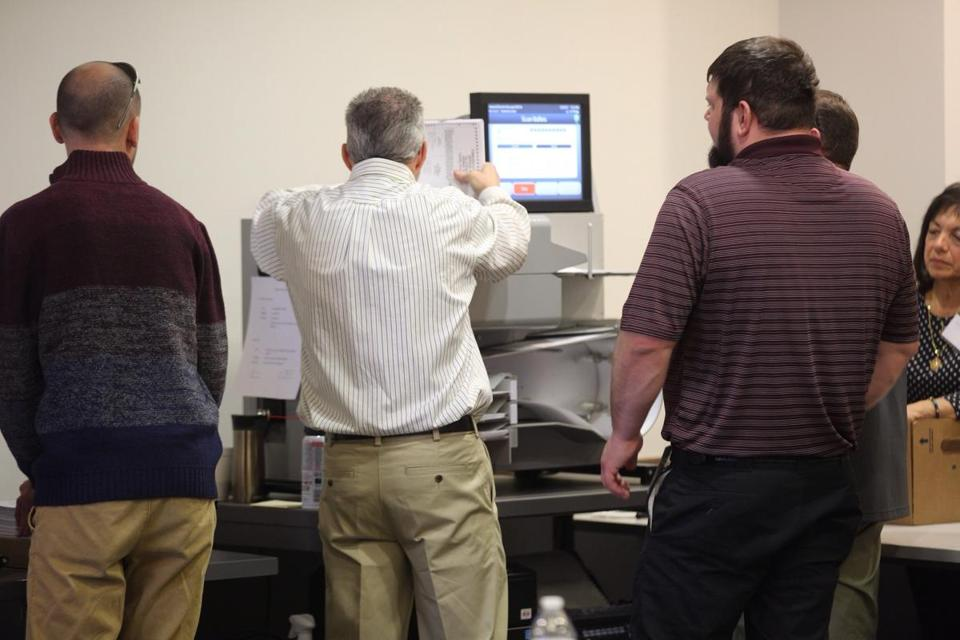 Officials use a high-speed machine on to recount results from the 94th District House of Delegates race at City Center in Newport News Va
