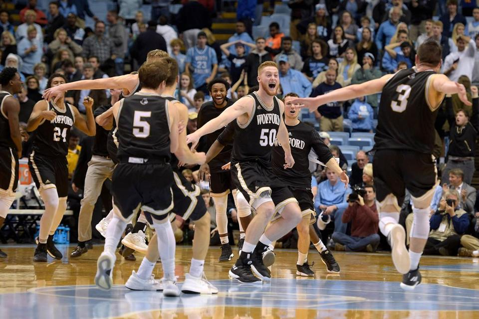 CHAPEL HILL, NC - DECEMBER 20: Matthew Pegram #50 and Fletcher Magee #3 of the Wofford Terriers celebrate with teammates following their win against the North Carolina Tar Heels at Dean Smith Center on December 20, 2017 in Chapel Hill, North Carolina. Wofford won 79-75. (Photo by Lance King/Getty Images)