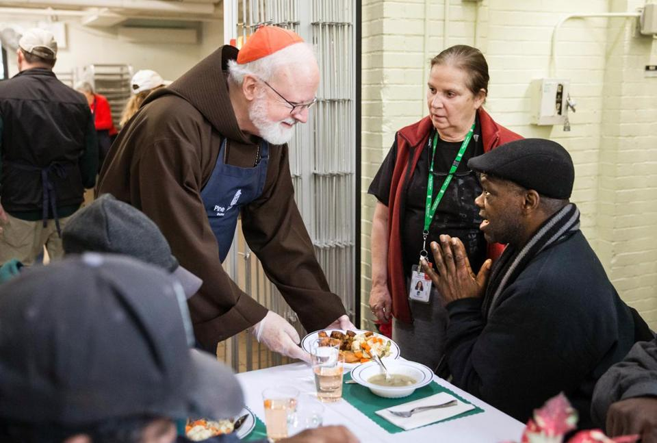 12/24/2017 BOSTON, MA Cardinal Seán O'Malley (cq) (left) served Jamil Abdallah (cq) during the Christmas Eve Luncheon held at the Pine Street Inn in Boston. (Aram Boghosian for The Boston Globe)