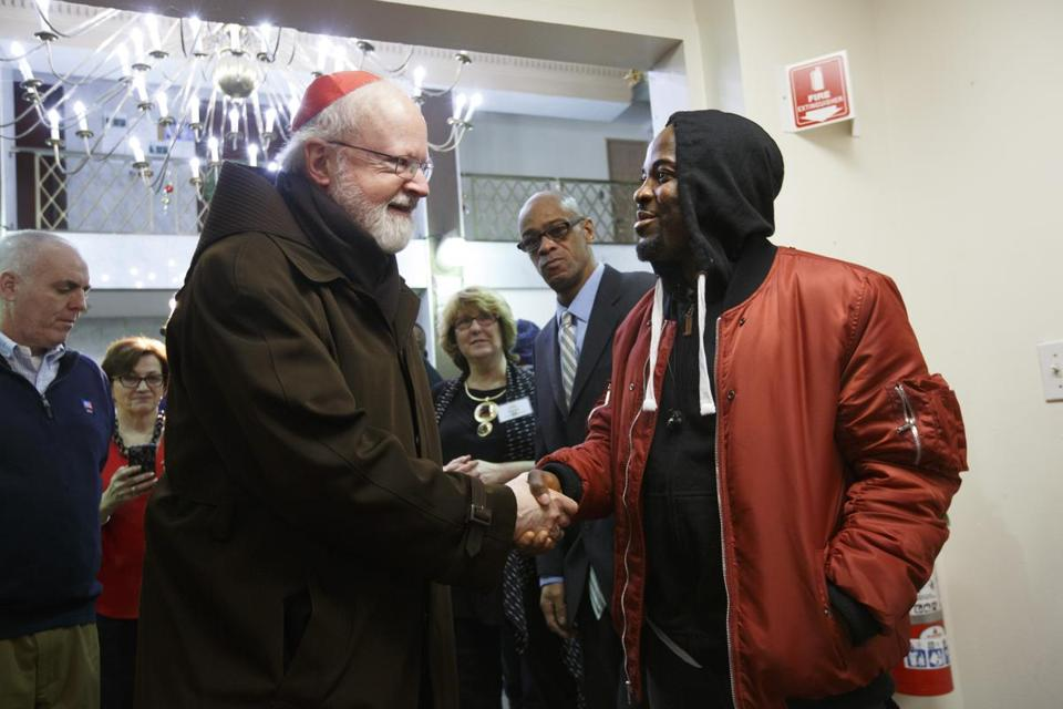 12/25/2017 - Boston, MA - Rolan Yarpah, cq, right, greeted Cardinal Sean O'Malley, cq, left, who visited the St. Francis House on Christmas morning and held a special service for residents and guests. Photo by Dina Rudick/Globe Staff