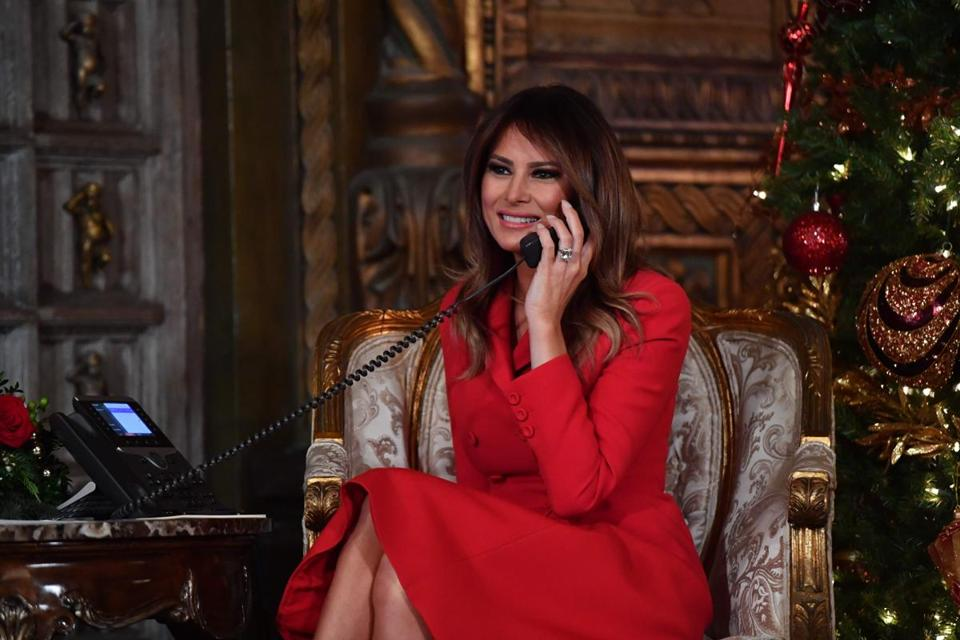 "First Lady Melania Trump participates in NORAD Santa Tracker phone calls at the Mar-a-Lago resort in Palm Beach, Florida on December 24, 2017. ""NORAD Tracks Santa"" is an annual Christmas-themed entertainment program, which has existed since 1955, produced under the auspices of the North American Aerospace Defense Command. / AFP PHOTO / Nicholas KammNICHOLAS KAMM/AFP/Getty Images"