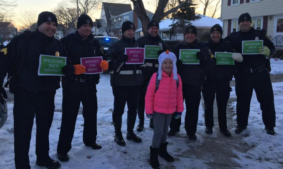 Quincy officers held signs for Bridget Kelley (front) as she returned to school Tuesday.