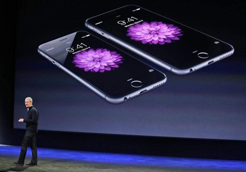 Apple CEO Tim Cook talks about the iPhone 6 and iPhone 6 Plus during an Apple event in San Francisco. Apple is apologizing for secretly slowing down older iPhones which it says was necessary to avoid unexpected