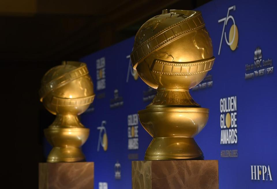 FILE - In this Monday, Dec. 11, 2017 file photo, Golden Globe statues appear on stage prior to the nominations for 75th Annual Golden Globe Awards at the Beverly Hilton hotel in Beverly Hills, Calif. The Golden Globe Awards will be handed out on Sunday, Jan. 7, 2018, at a ceremony is being held under the cloud of the sexual misconduct scandal that started with several high-profile actresses accusing Harvey Weinstein of sexual harassment or abuse. Many actresses say they are planning to wear black Sunday to show solidarity with victims of harassment and abuse. (Photo by Chris Pizzello/Invision/AP, File)