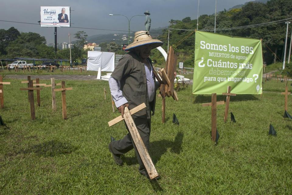 A city employee removes wooden crosses that were placed in a plaza by organizations protesting against the government inaction over the alarming murder rate in San Salvador, El Salvador, Tuesday Sept. 1, 2015. Figures released by the country's coroner's office confirm the month of August as the deadliest in the country's history. (AP Photo/Salvador Melendez)