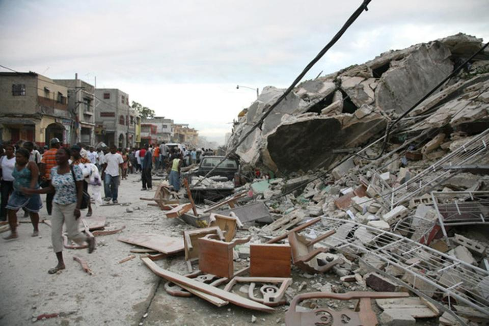 Haitians walk past damaged buildings on January 12, 2010 in Port-au-Prince after a huge earthquake measuring 7.0 rocked the impoverished Caribbean nation of Haiti, toppling buildings and causing widespread damage and panic, officials and AFP witnesses said. A tsunami alert was immediately issued for the Caribbean region after the earthquake struck at 2153 GMT. AFP PHOTO / Lisandro SUERO == RESTRICTED TO EDITORIAL USE / NO SALES == (Photo credit should read LISANDRO SUERO/AFP/Getty Images) Library Tag 01132010