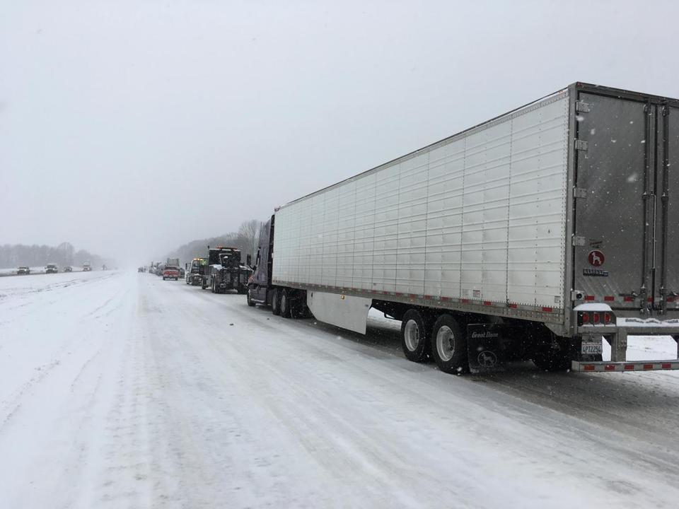 A line of semi-trucks, tow trucks and cars sits stationary on Interstate 40 westbound as road crews clear up an accident on Friday, Jan. 12, 2018, near Henderson, Tenn. The winter storm, which began with an icy mix before turning to snow, forced schools and businesses to close in Tennessee and Kentucky. Hardest hit were western parts of both states. (AP Photo/Adrian Sainz)