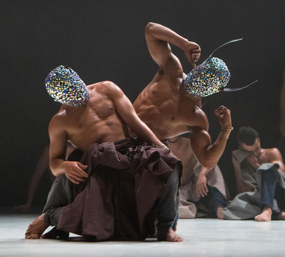 In part of the performance, dancers wear masks that glitter like disco balls and have knife-like horns.
