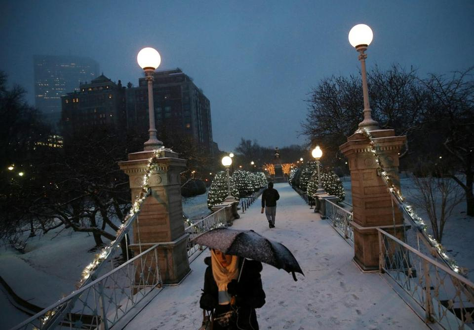 Pedestrians passed over the Lagoon as snow falls at the Public Garden in Boston on Wednesday.