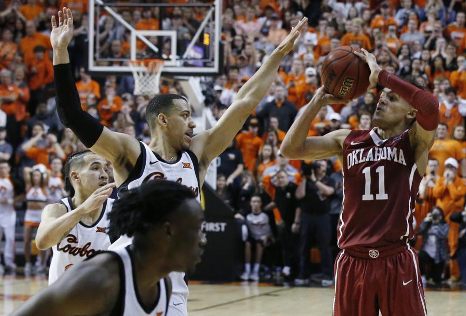 Oklahoma guard Trae Young (11) takes the final shot of overtime in front of Oklahoma State guard Kendall Smith, left, in an NCAA college basketball game against in Stillwater, Okla., Saturday, Jan. 20, 2018. Oklahoma State won 83-81 in overtime. (AP Photo/Sue Ogrocki)