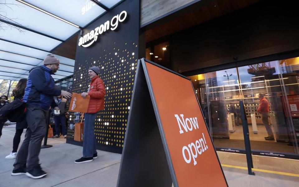 A customer is handed a complimentary shopping bag as he heads into an Amazon Go store, Monday, Jan. 22, 2018, in Seattle. More than a year after it introduced the concept, Amazon opened its artificial intelligence-powered Amazon Go store in downtown Seattle on Monday. The store on the bottom floor of the company's Seattle headquarters allows shoppers to scan their smartphone with the Amazon Go app at a turnstile, pick out the items they want and leave. (AP Photo/Elaine Thompson)