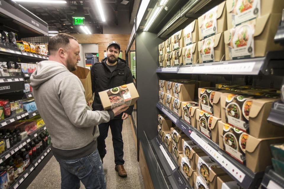 SEATTLE, WA - JANUARY 22: Shoppers Peter Freese, right, and Peter Ray check out pre-made meals at the Amazon Go January 22, 2018 in Seattle, Washington. After more than a year in beta Amazon opened the cashier-less store to the public. (Photo by Stephen Brashear/Getty Images)
