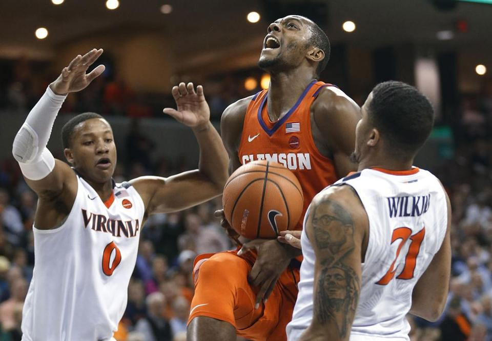 Clemson forward Aamir Simms (25) loses the ball as Virginia guard Devon Hall (0) and forward Isaiah Wilkins (21) defend during the first half of an NCAA college basketball game in Charlottesville, Va., Tuesday, Jan. 23, 2018. (AP Photo/Steve Helber)