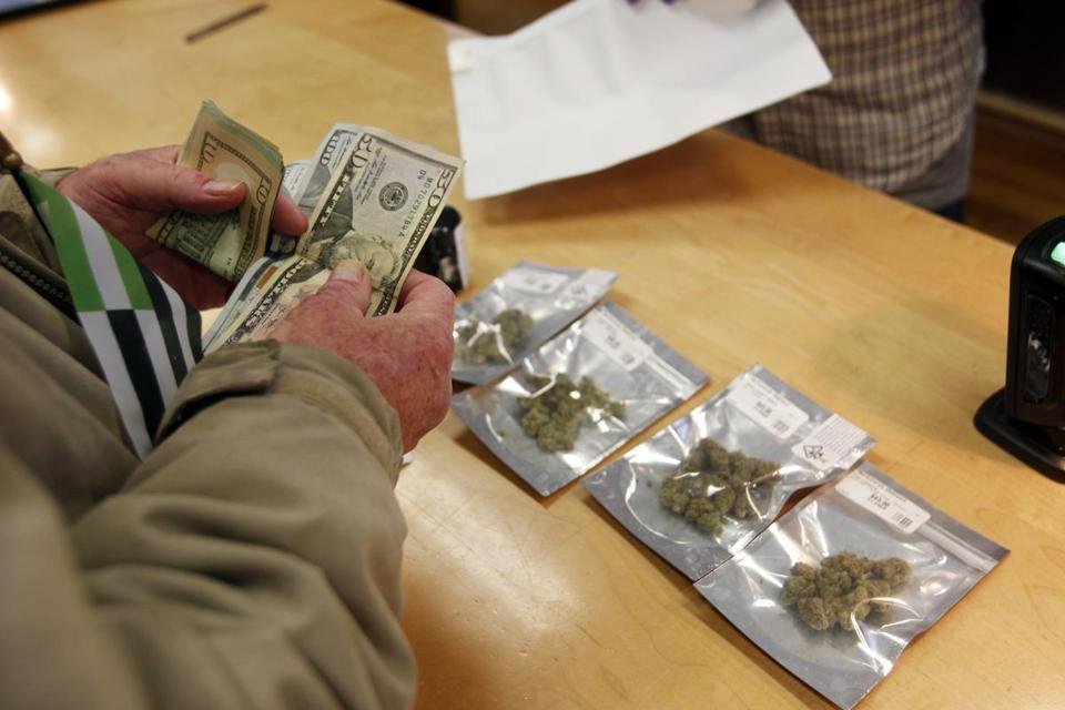 FILE - In this Monday, Jan. 1, 2018 file photo, a customer purchases marijuana at the Harborside marijuana dispensary in Oakland, Calif., on the first day that recreational marijuana was sold legally in California. In January 2018, Attorney General Jeff Sessions rescinded a 2013 Obama Administration policy pledging that federal authorities would not crack down on marijuana operations in states where they were legal as long as the states maintained tight regulations. (AP Photo/Mathew Sumner)