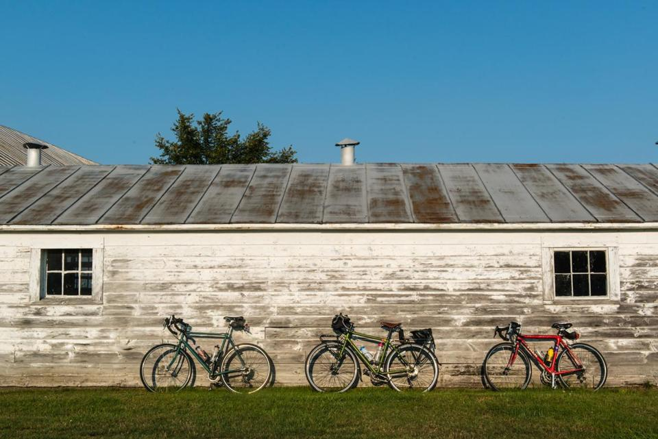 Bikes rest against a barn at Mountain Village Farm B&B in Kingfield, Maine, where the hosts for the night provided field space for tents, support vehicles, a dinner tent, and a barn dance with a live band.