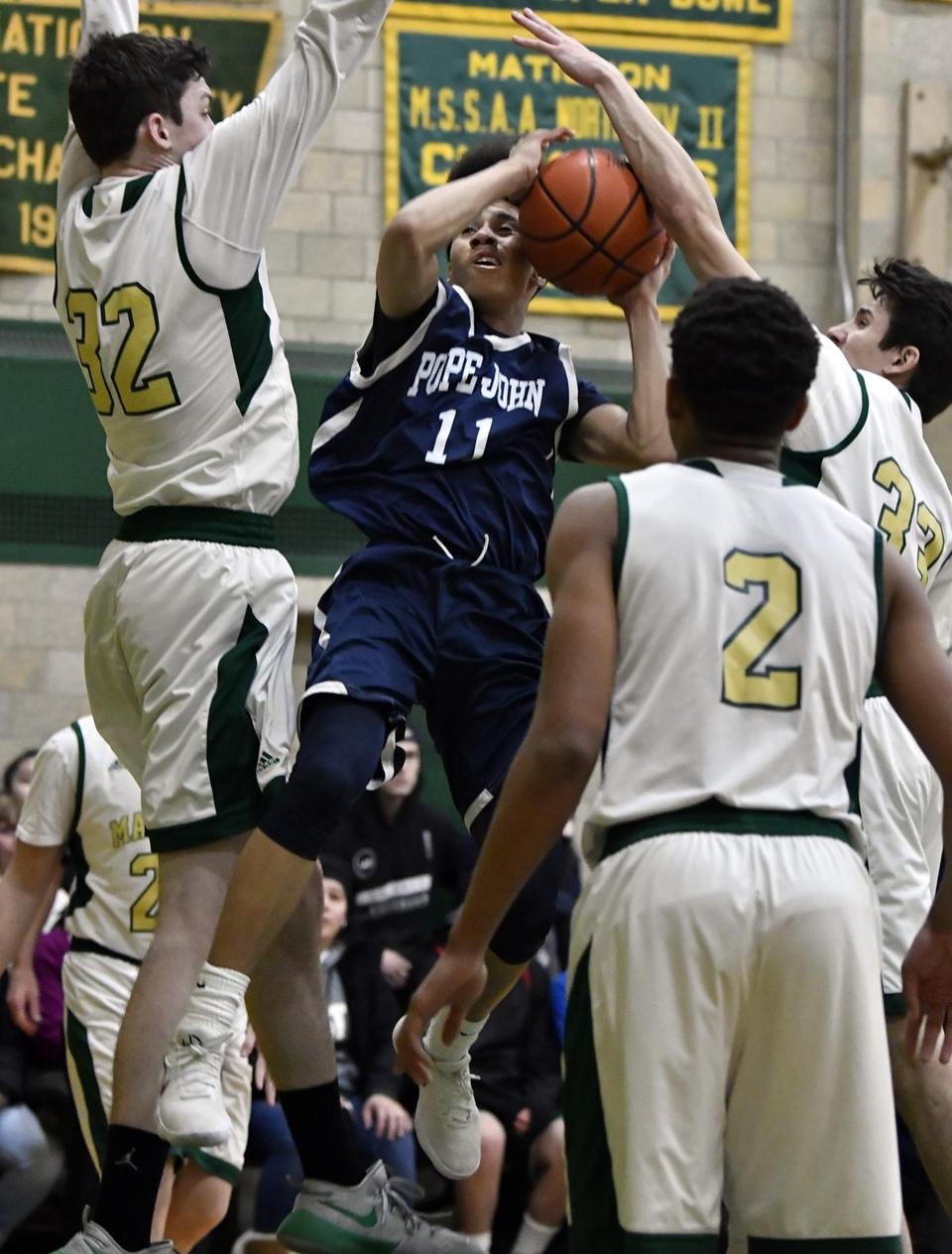 Pope John's Angel Price-Espada finds himself surrounded by Matignon's Conner Byrne (32). Jayson Clayton (2), and Philip Trapani (33)  during their game Friday in Cambridge.