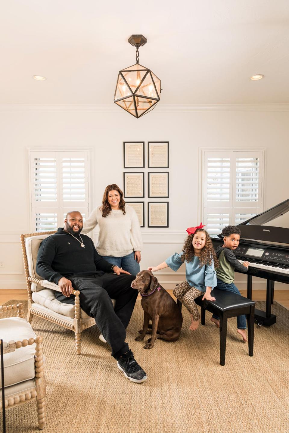 "Marcus, Alyssa, Mady, M.J., and one of the family's two Labradors gather near the piano. ""It's a place dedicated to playing and listening,"" designer Kelly McGuill says of the music room."