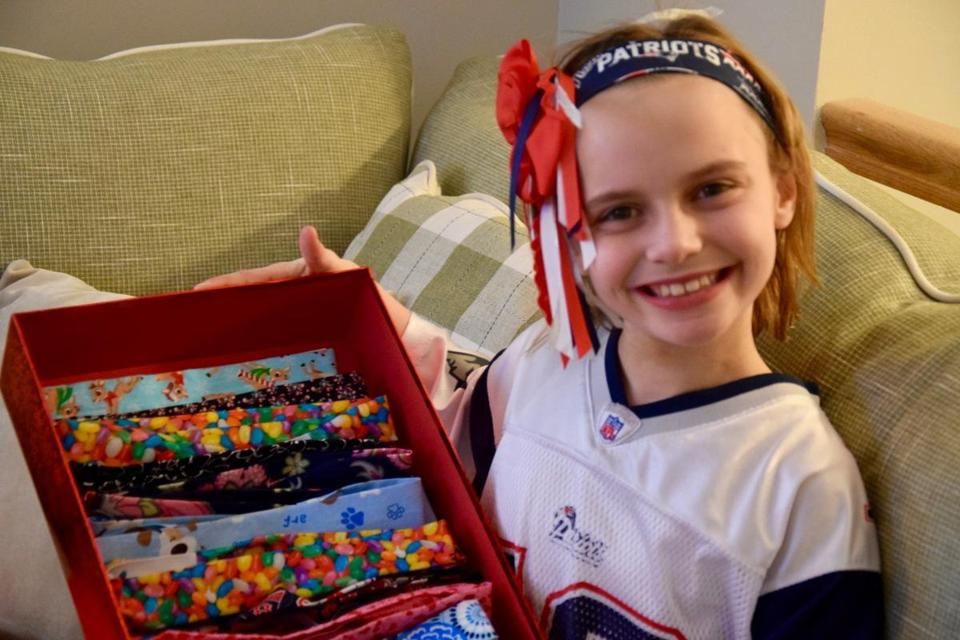 Quincy third-grader Elizabeth Dawe on Super Bowl Sunday with some of the headbands she made to support Boston Children's Hospital.