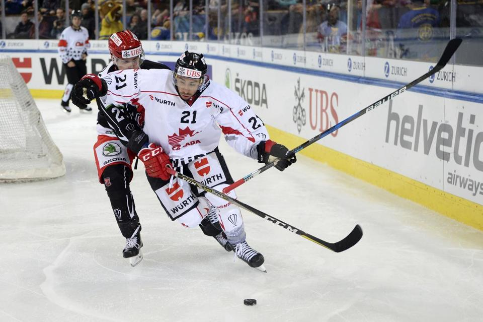 Mountfield's Oskars Cibulskis, left, battles for the puck with Team Canada's Chris Kelly during the game between Team Canada and Mountfield HK at the 91st Spengler Cup ice hockey tournament in Davos, Switzerland, Tuesday, Dec. 26, 2017. (Melanie Duchene/Keystone via AP)