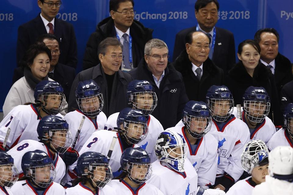 The first lady Kim Jung-sook, from left, South Korean President Moon Jae-in, IOC president Thomas Bach, North Korea's nominal head of state Kim Yong Nam and Kim Yo Jong, sister of North Korean leader Kim Jong Un, take a group photo with the combined Koreas team after the team's preliminary round of the women's hockey game against Switzerland at the 2018 Winter Olympics in Gangneung, South Korea, Saturday, Feb. 10, 2018. (AP Photo/Jae C. Hong)