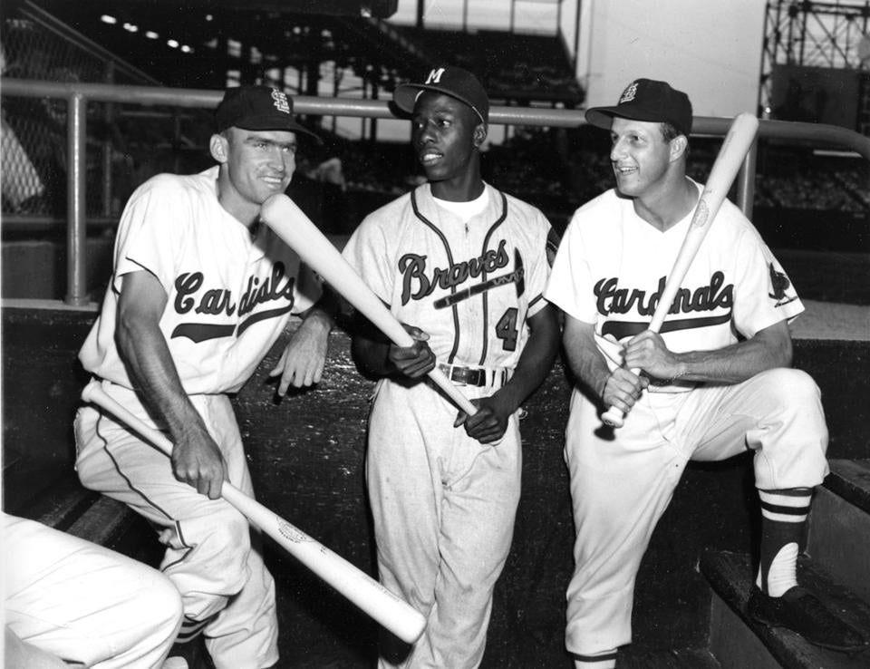 St. Louis Cardinals players Wally Moon (left) and Stan Musial flanked Milwaukee Braves outfielder Hank Aaron.